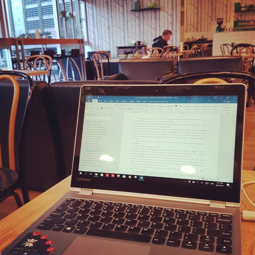 Small laptop on a cafe table with a view of The Annexe