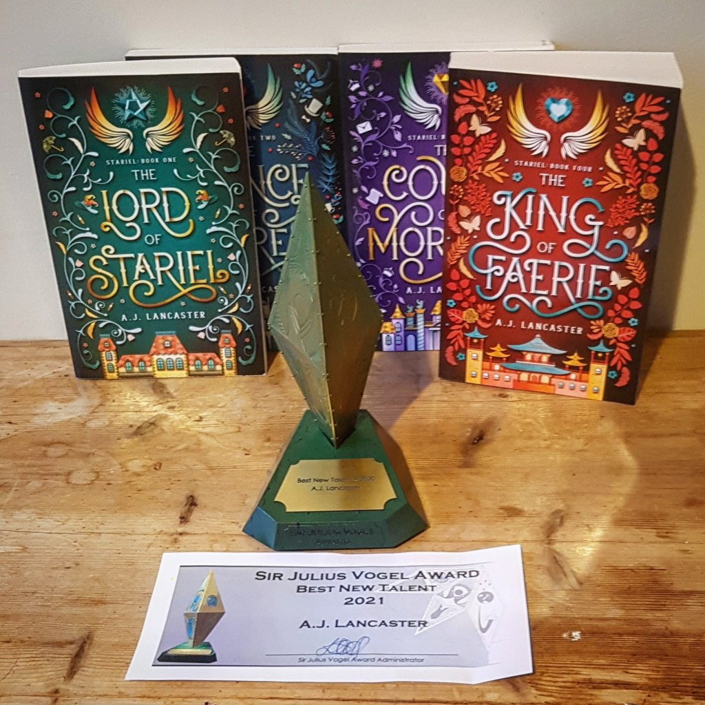 A gold and green trophy shaped like a diamond placed in front of the four books from the Stariel series.